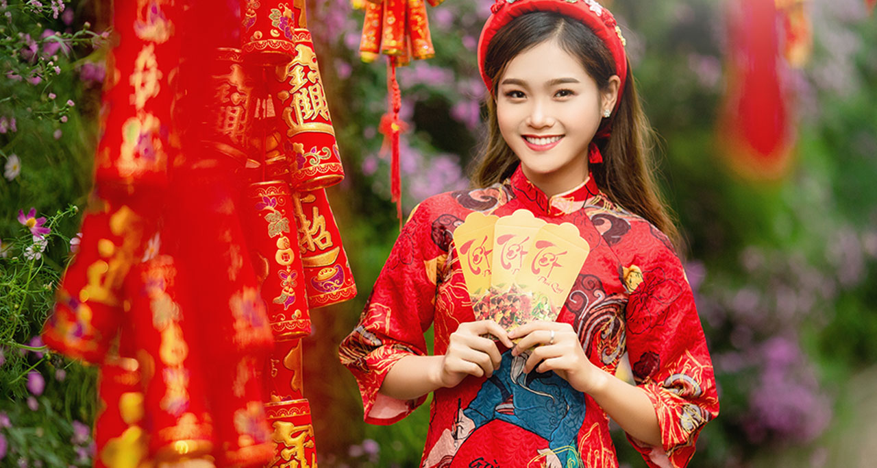 "Vietnamese Girl in Traditional Dress with ""red envelope"" on the Lunar New Year"